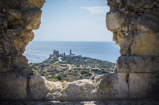 Vista do farol através do buraco na parede de pedra, Masua, Cagliari, Sardenha, Itália — Fotografia de Stock
