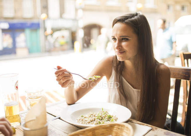 Young woman having lunch in restaurant — Stock Photo