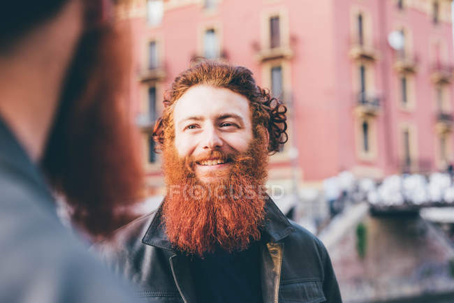Young male hipster twins with red hair and beards talking on street — Stock Photo