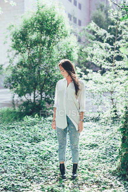Портрет молодой женщины, смотрящей вниз в сад офисного здания — стоковое фото