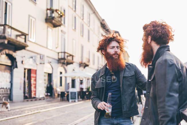 Jovens gêmeos hipster do sexo masculino com cabelos vermelhos e barbas falando na rua da cidade — Fotografia de Stock