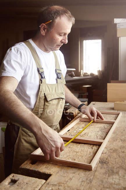 Man carpenter measuring frame at workbench — Stock Photo