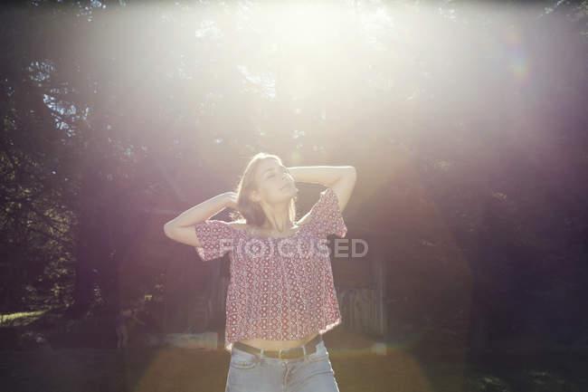Молодая женщина с закрытыми глазами в солнечном лесу, Sattelbergalm, Тироль, Австрия — стоковое фото