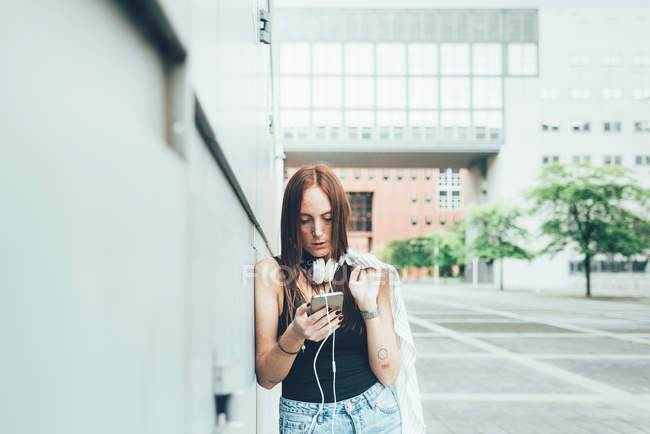 Young woman leaning against wall reading smartphone texts — Stock Photo