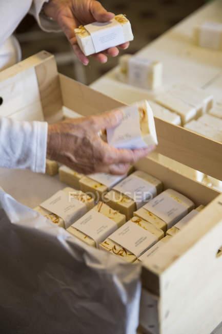 Женские руки, упаковка баров мыло в мастерской мыло ручной работы — стоковое фото