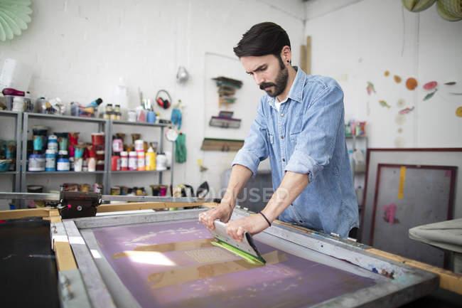Jovem macho impressora usando o rodo no estúdio de impressão — Fotografia de Stock