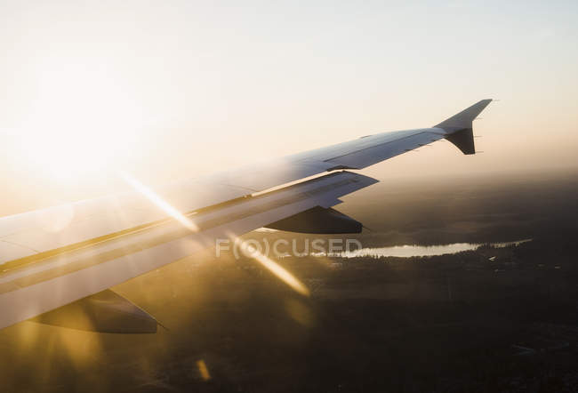 Vista elevata dell'ala dell'aereo sul paesaggio sagomato al tramonto, Finlandia — Foto stock