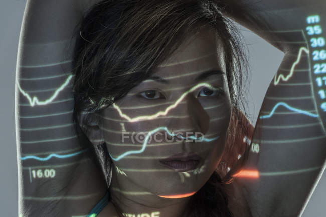 Woman exercising against grey background with graphs and data projected onto face — Stock Photo