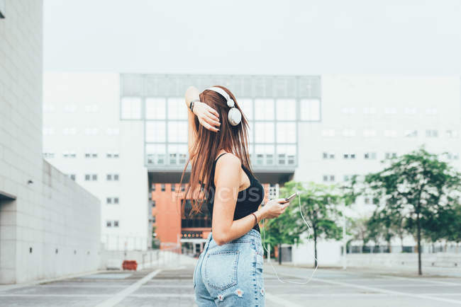 Young woman listening to headphones with hand on head outside office building — Stock Photo