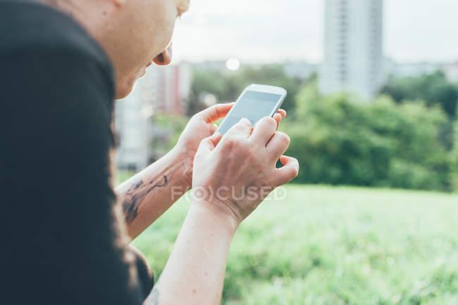 Куповані постріл жінка на траві за допомогою сенсорного екрану смартфона — стокове фото