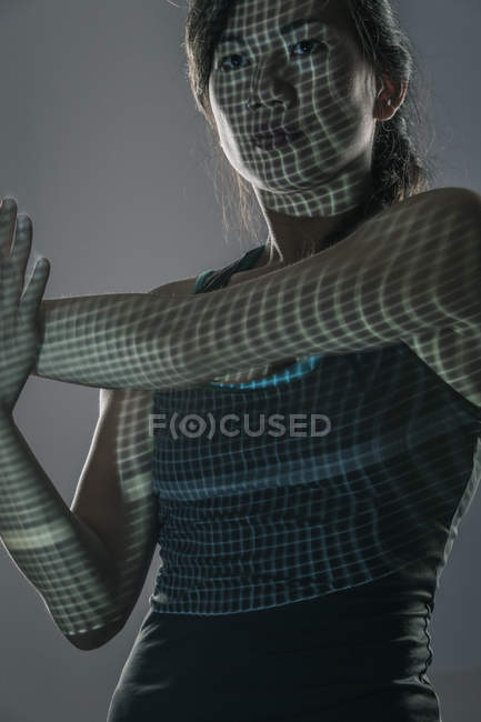 Mid adult woman against grey background, exercising, grid projected onto face and body — Stock Photo