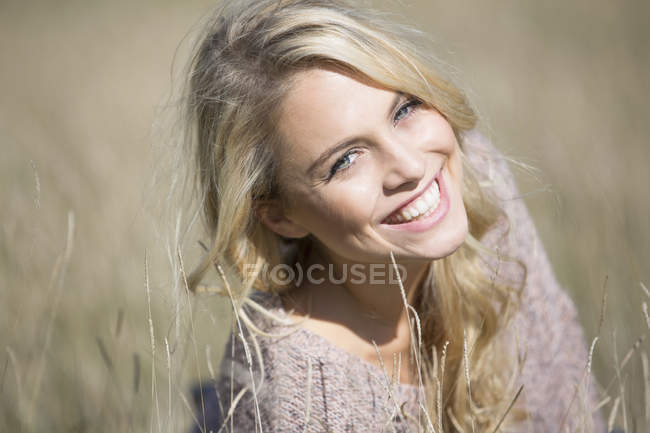Portrait of young woman in long grass, smiling — Stock Photo