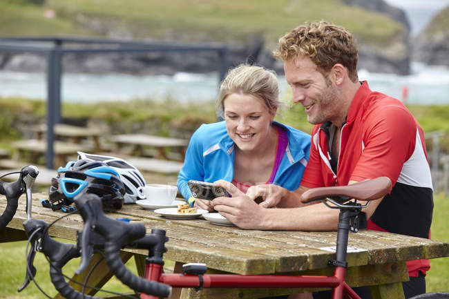 Cyclists using mobile phone at picnic table overlooking ocean — Stock Photo