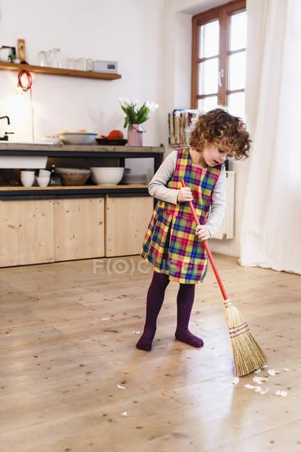 Cute girl sweeping kitchen floor — Stock Photo