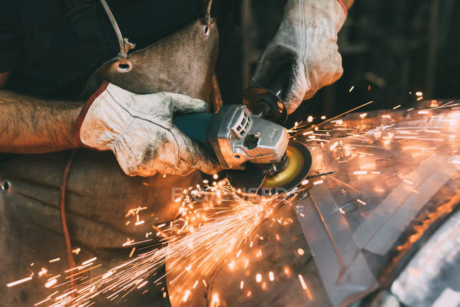 Hands of metalworker grinding copper in forge workshop — Stock Photo