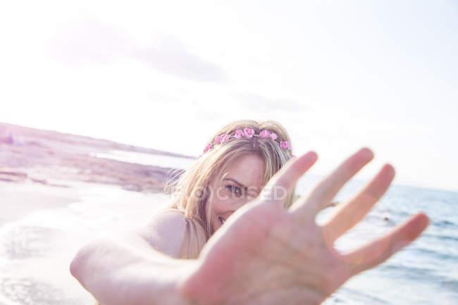 Женщина, прикрывающая лицо на пляже — стоковое фото