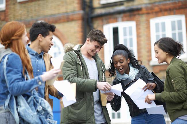 Щасливі молодих дорослих студентів читання результати іспиту на кампусі — стокове фото