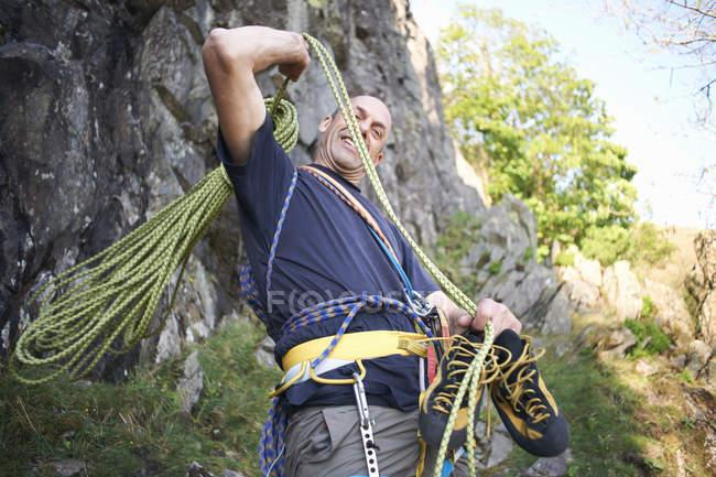 Скеля climber підготовка скелелазіння мотузки, посміхаючись — стокове фото