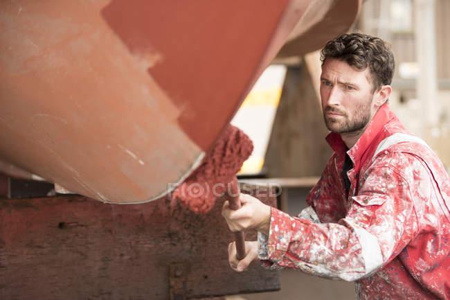Peintre de navire mâle rouleau peinture coque de navire rouge dans la cour des peintres de navire — Photo de stock