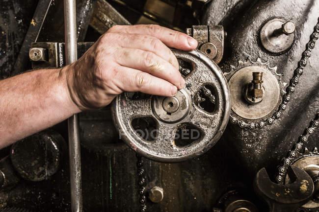 Close-up de mans mão operam máquinas de impressão na oficina de prensa — Fotografia de Stock