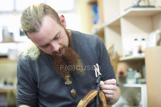 Male worker in leather workshop, sewing up seams around a belt buckle — Stock Photo