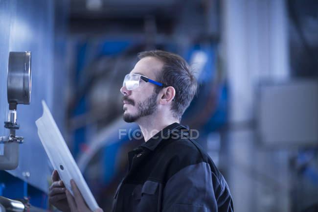 Jovem adulto masculino engenheiro verificando manômetro — Fotografia de Stock