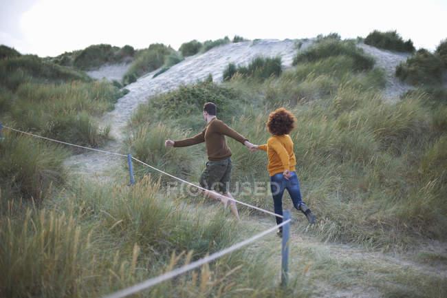 Casal correndo em Duna gramada — Fotografia de Stock