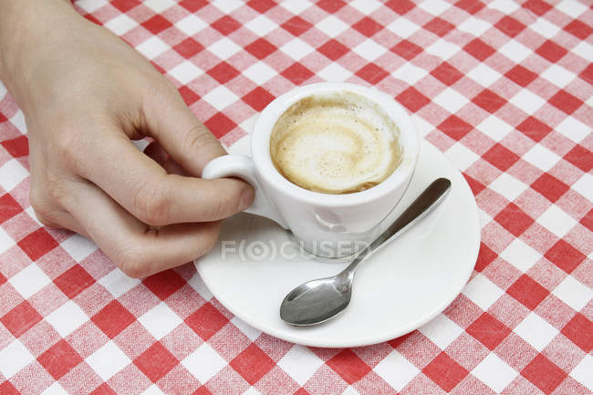 Female hand with espresso at sidewalk cafe table, Milan, Italy — Stock Photo