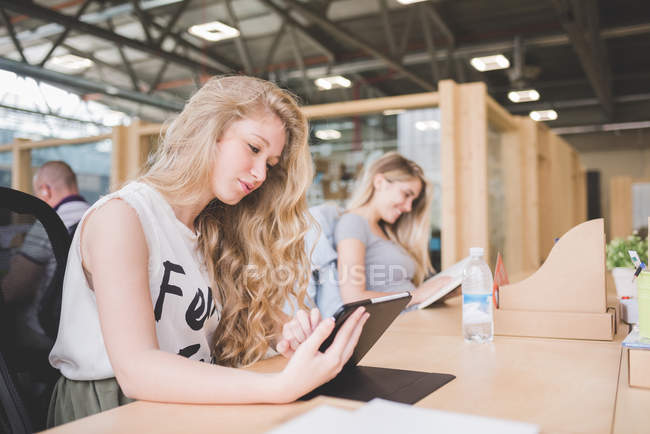 Коллеги, работающие над цифровым планшетом в офисе открытого плана — стоковое фото