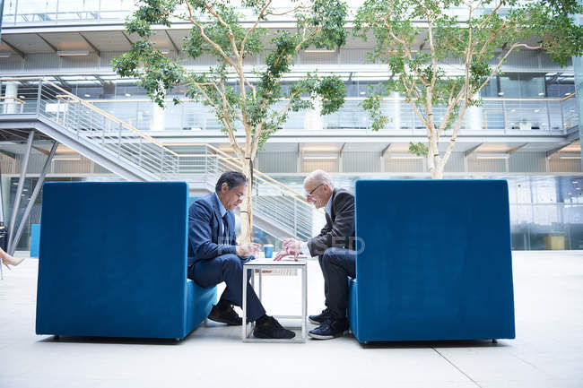 Two businessmen having discussion meeting in office atrium armchairs — Photo de stock