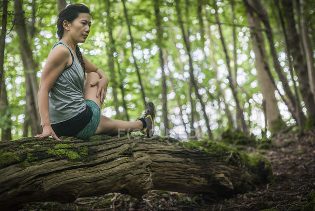 Woman exercising and stretching in forest — Stock Photo