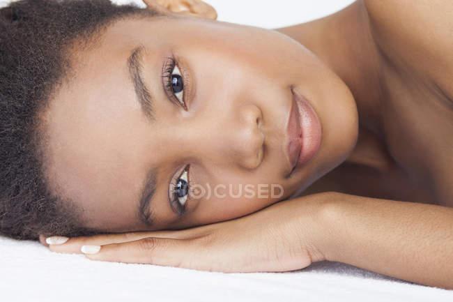 Headshot de mulher deitada olhando para a câmera — Fotografia de Stock