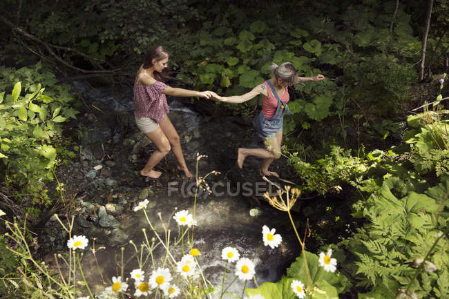 Two female friends crossing stream, Sattelbergalm, Tyrol, Austria — Stock Photo