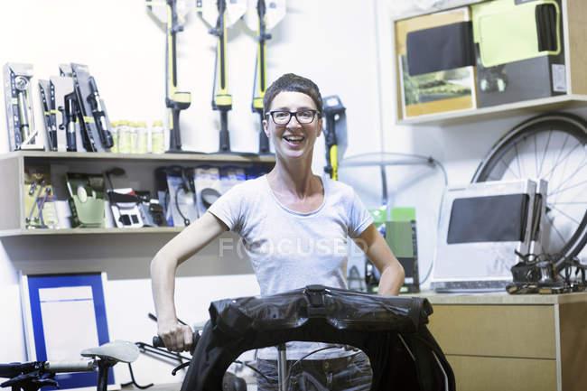 Жінка в майстерні проведення лежачому велосипеді, дивлячись на камеру посміхаючись — стокове фото