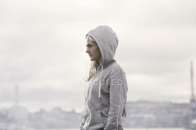 Female runner in grey hoody on misty dockside — Stock Photo