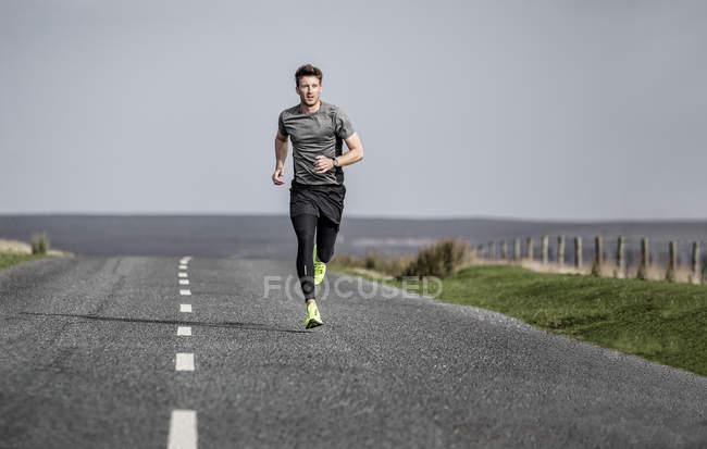 Male runner running along rural moorland road — Stock Photo