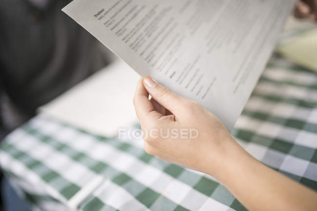 Cropped view of woman's hands holding menu — Stock Photo