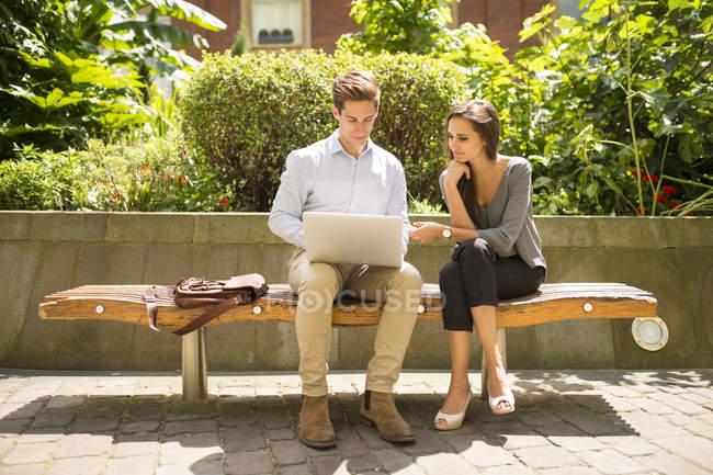 Giovane donna d'affari e uomo che utilizza il computer portatile su panchina, Londra, Regno Unito — Foto stock