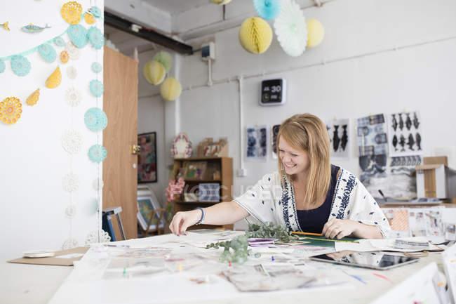Diseñadora femenina preparando diseño de medios mixtos en estudio de impresión - foto de stock