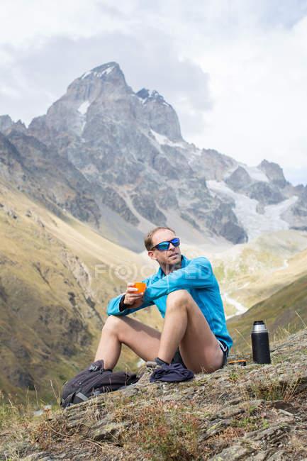 Caminhante masculino fazendo uma pausa para café na paisagem da montanha, Ushba, Svaneti, Geórgia — Fotografia de Stock
