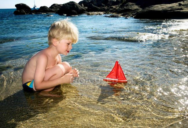 Хлопчик грає з іграшкою вітрильник — стокове фото
