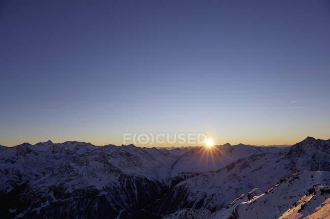 Regolazione sun sopra l'intervallo di montagna innevata — Foto stock