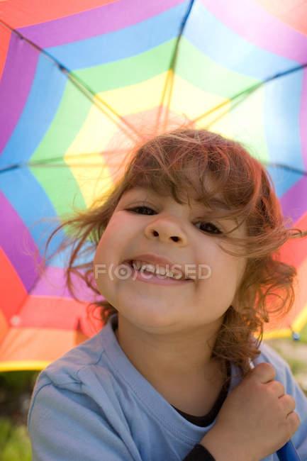 Chica joven bajo paraguas multicolores - foto de stock