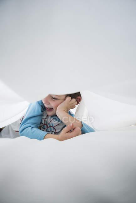 Junge liegt auf der Seite zwischen weißen Bettlaken — Stockfoto