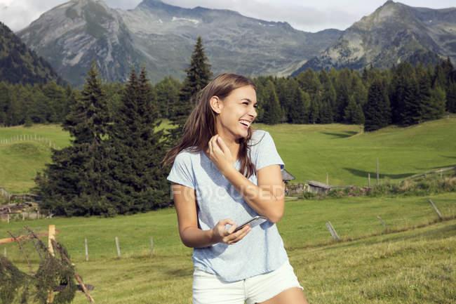 Молода жінка тримає смартфон і сміятися в австрійських Альпах, Sattelbergalm, Тіроль, Австрія — стокове фото