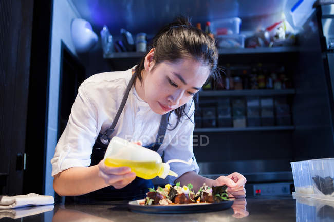 Asian chef dressing prepared meal in kitchen — Stock Photo