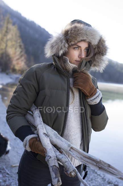 Frau mit Pelzmütze trägt Brennholz am Seeufer in bayerischen Alpen — Stockfoto