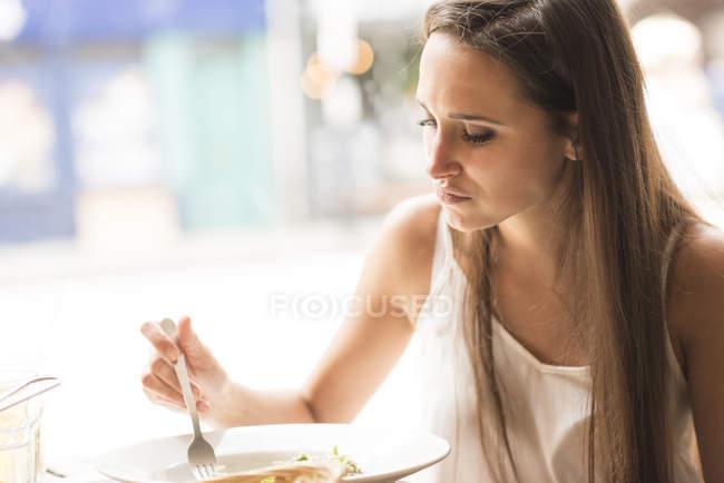Молодая женщина обедает в ресторане — стоковое фото