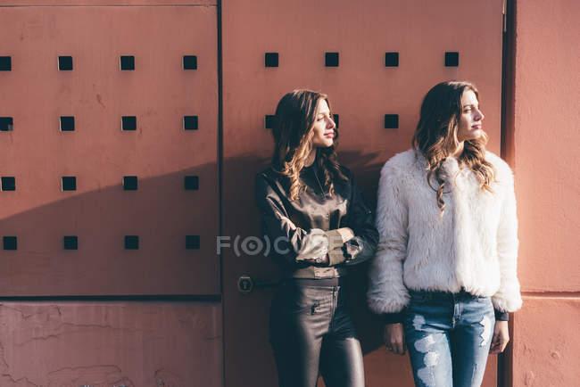 Ritratto di due sorelle gemelle, all'aperto, che si appoggia contro la parete, distogliendo lo sguardo — Foto stock
