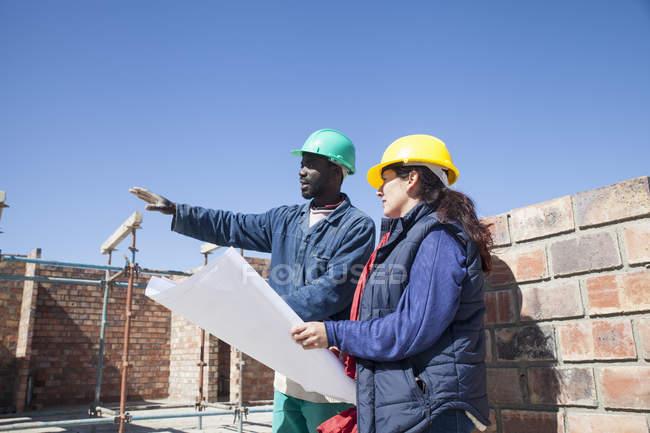 Руководитель и строитель объекта рассматривает чертежи строительных площадок — стоковое фото